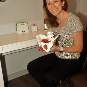 Pelvic Physiotherapist Lauren Campbell holds a model pelvis